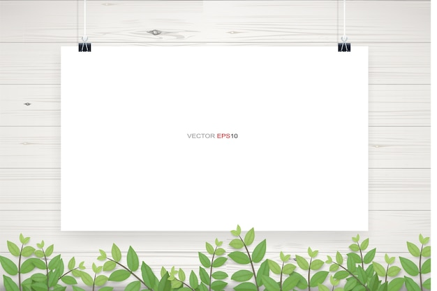 Affiche de papier blanc accroché sur fond de texture de mur en bois blanc avec cadre de feuilles vertes