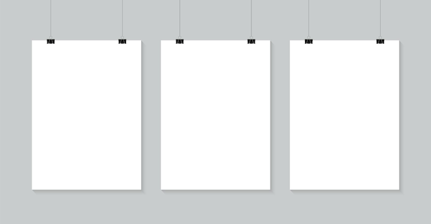 Affiches vierges accrochées à des clips de reliure. une feuille de papier blanc a4 est suspendue à une corde avec une bannière de clips pour la promotion et la publicité.