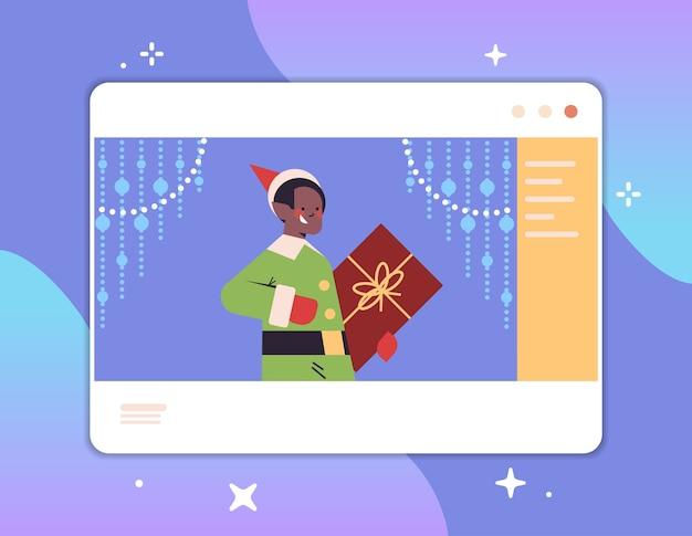 African american boy elf holding boîte-cadeau dans la fenêtre du navigateur web bonne année joyeux noël vacances célébration concept communication en ligne auto-isolement portrait horizontal illustration vectorielle