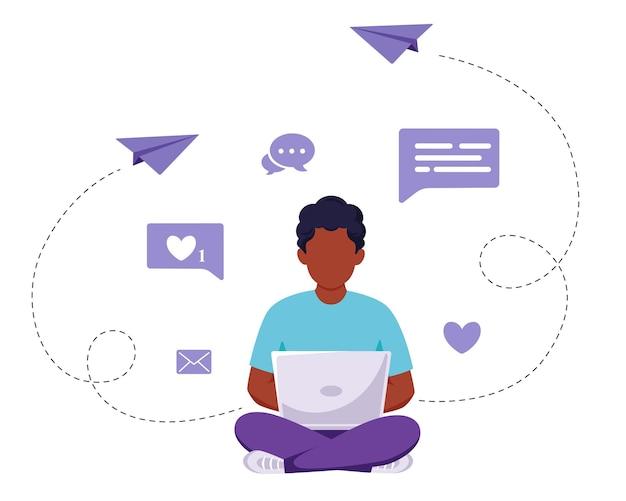 Afro-américain assis avec un ordinateur portable