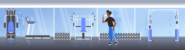Afro-américain, athlète fitness, homme, eau potable, depuis, bouteille plastique, après, séance entraînement, exercice, sain, style de vie, concept, moderne, gymnase, intérieur, horizontal, longueur