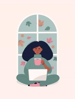 Afro femme buvant du café et travaillant sur ordinateur portable par fenêtre