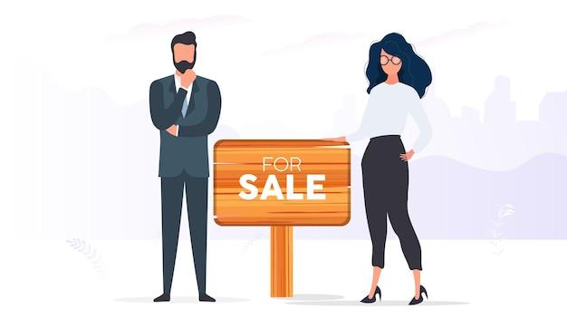 Agents immobiliers avec un signe à vendre. la fille et l'homme sont des agents immobiliers. bon pour la conception sur le thème de la vente de maisons, d'appartements et de biens immobiliers. vecteur.