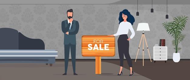 Agents immobiliers avec un signe à vendre. la fille et l'homme sont des agents immobiliers. le concept de vente d'appartements, de maisons et de biens immobiliers. isolé. vecteur.