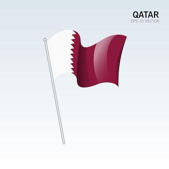 Agitant le drapeau du qatar isolé sur gris