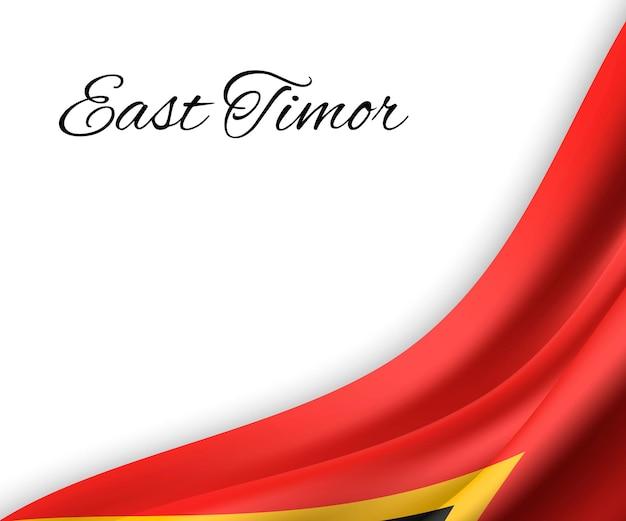 Agitant le drapeau du timor oriental sur fond blanc.