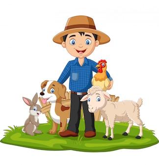 Agriculteur avec des animaux de ferme dans l'herbe