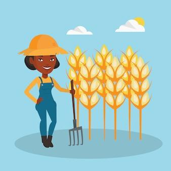 Agriculteur avec fourche au champ de blé.