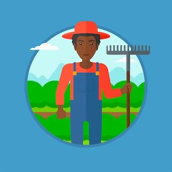 Agriculteur avec râteau au champ de chou.