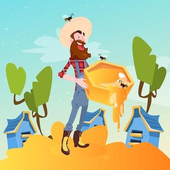 Un agriculteur recueille du miel dans un rucher de ruche