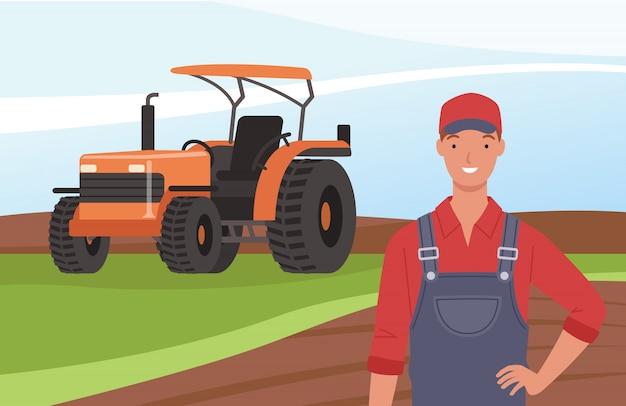 Agriculteur souriant sur l'arrière-plan d'un champ et d'un tracteur.