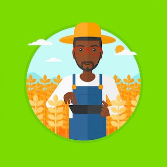 Agriculteur avec tablette sur champ.