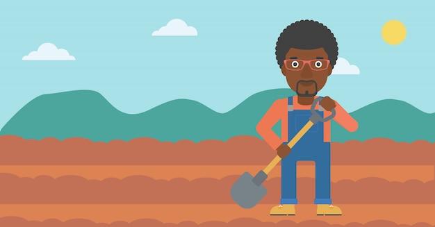 Agriculteur sur le terrain avec une pelle