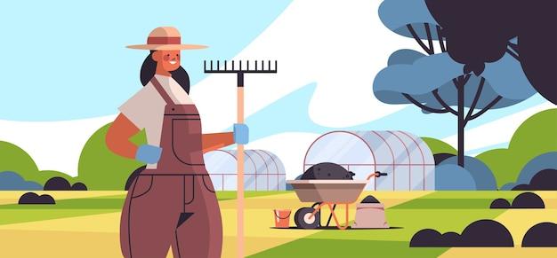 Agricultrice en uniforme tenant râteau eco agriculture agriculture concept rural terres agricoles campagne paysage portrait horizontal illustration vectorielle