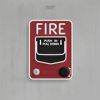 Alarme incendie rouge sur fond de béton gris.