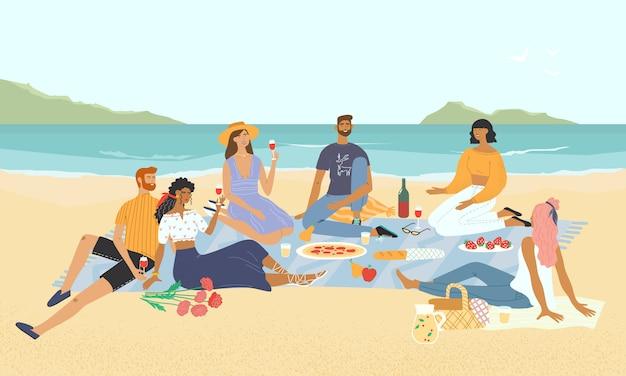Amis souriants se détendre lors d'un pique-nique au bord de la mer. heureux hommes et femmes buvant du vin et mangeant de la nourriture sur la plage. groupe de personnes élégantes en train de déjeuner avec vue sur le paysage marin en arrière-plan.
