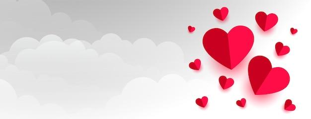 Amour coeurs de papier sur la bannière de la saint valentin nuages