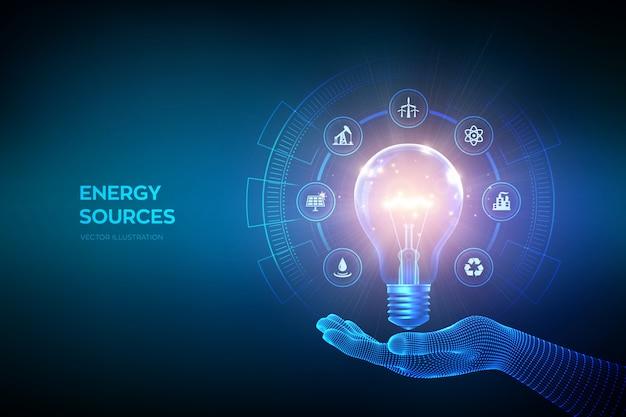 Ampoule rougeoyante avec des icônes de ressources énergétiques à la main. concept d'économie d'électricité et d'énergie. sources d'énergie.