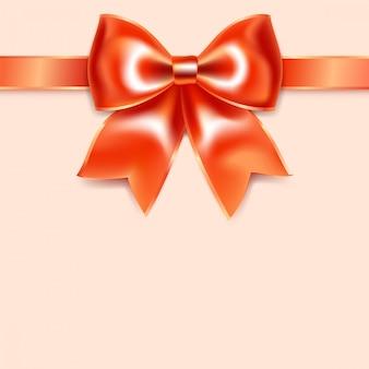 Arc rouge de ruban de soie, isolé sur fond rose