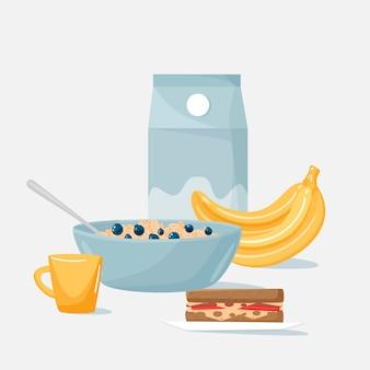 Une assiette de flocons d'avoine, du lait et une tasse de thé, un sandwich et des bananes.