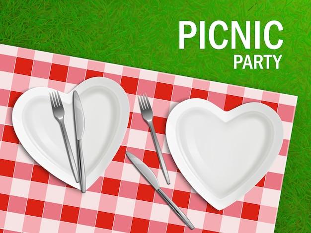 Assiette en forme de coeur sur la nappe et l'herbe verte