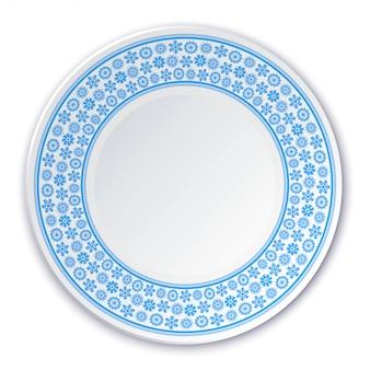 Assiette en porcelaine sur un tableau de flocons de neige bleus sur fond blanc