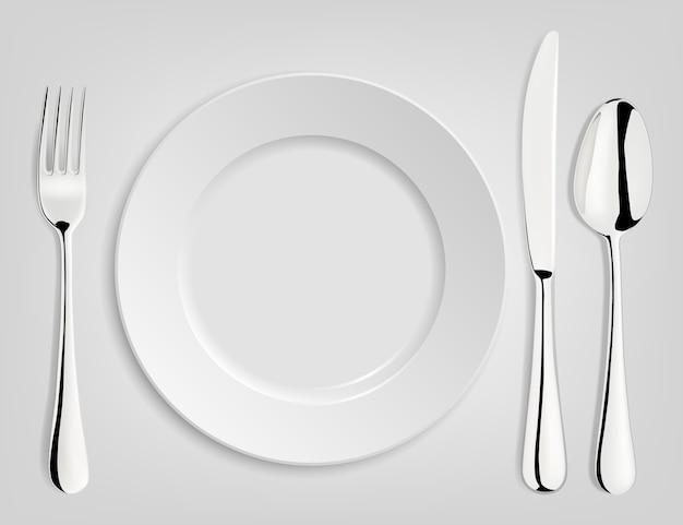 Assiette vide avec cuillère, couteau et fourchette.