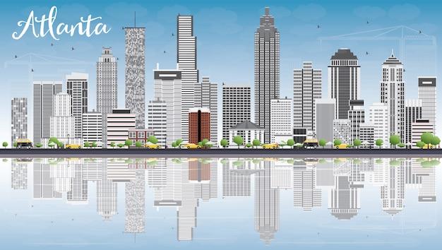 Atlanta skyline avec bâtiments gris, ciel bleu et reflets.