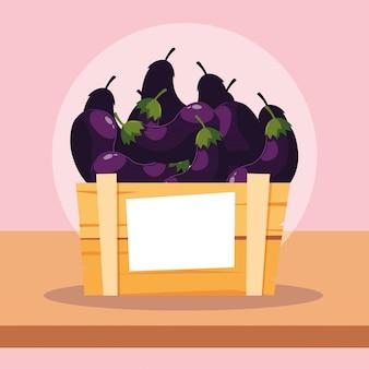 Aubergines fraîches dans une caisse en bois