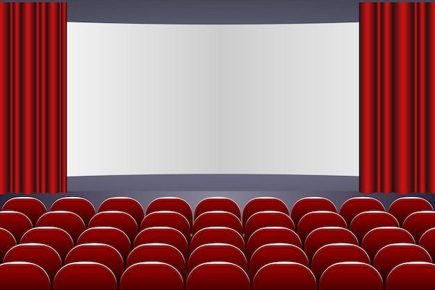 Auditorium de théâtre avec rangées de sièges rouges et scène avec rideau