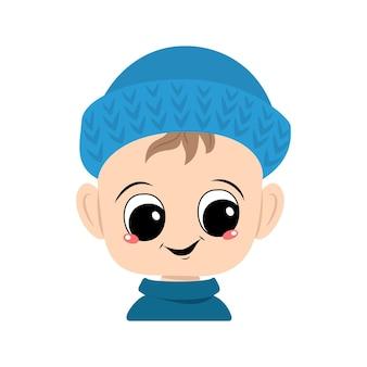 Avatar d'un enfant avec de grands yeux et un large sourire dans un bonnet bleu. un enfant mignon avec un visage joyeux dans une coiffe d'automne ou d'hiver. tête d'enfant en bas âge adorable avec des émotions heureuses