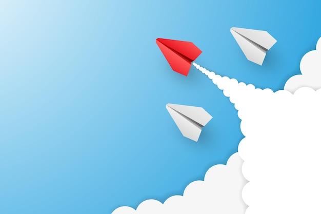 Avion en papier de leader rouge individuel en mènent d'autres avec des nuages