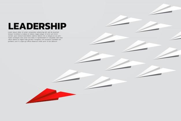 Avion en papier origami rouge menant groupe de blanc