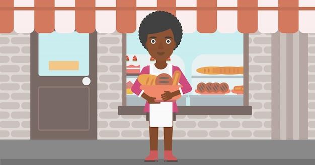 Baker tenant un panier avec des produits de boulangerie.