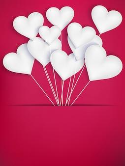 Ballons coeur saint valentin sur fond rouge.