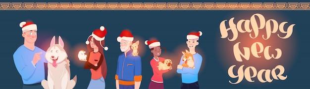 Bannière horizontale de vacances d'hiver avec groupe de personnes portant des chapeaux de père noël avec un chien mignon, bonne année