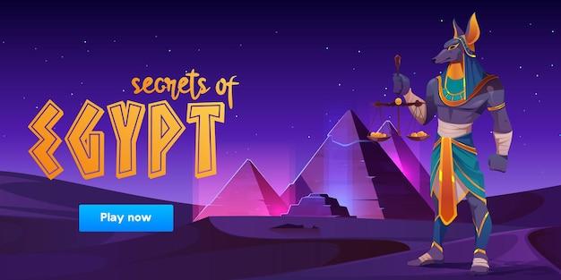Bannière de jeu sur les secrets de l'égypte avec anubis et pyramides sur un paysage désertique.
