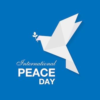 Bannière de la journée internationale de la paix avec colombe en papier blanc avec feuille sur fond bleu. illustration vectorielle eps10