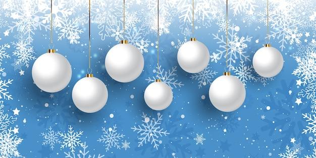 Bannière de noël avec des boules suspendues sur une conception de flocon de neige