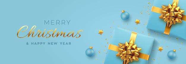 Bannière de noël. coffrets cadeaux bleus réalistes avec noeud doré, étoiles dorées, boules et confettis scintillants.