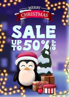 Bannière de réduction de noël avec guirlande et pingouin en chapeau de père noël avec des cadeaux.