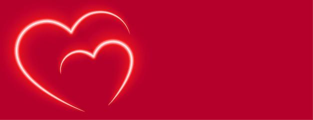 Bannière de la saint valentin deux coeurs rouges néon d'amour
