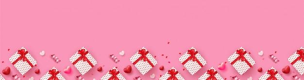 Bannière de la saint-valentin heureuse avec des coeurs de luxe rouges et roses, boîte-cadeau, ruban et beaux éléments.