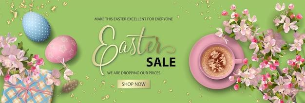 Bannière de vacances de pâques avec une tasse de café, des œufs et des fleurs de cerisier