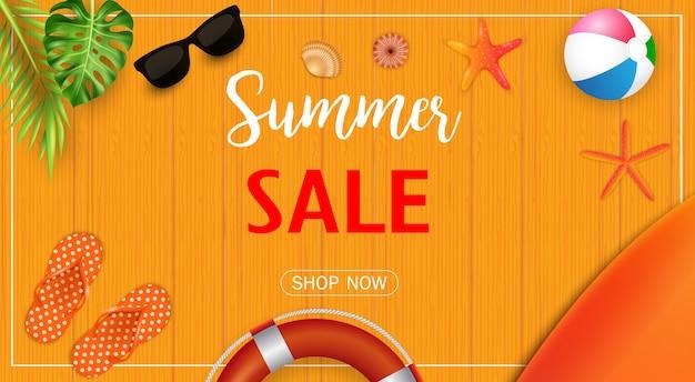 Bannière de vente de l'été avec des éléments de la plage sur la texture en bois