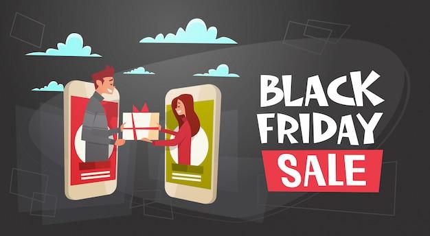 Bannière de vente vendredi noir avec l'homme donnant à la femme une boîte présente à travers une tablette numérique