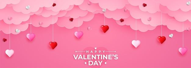 Bannière de voeux joyeuse saint valentin dans un style réaliste de papier découpé. coeurs et nuages de papier