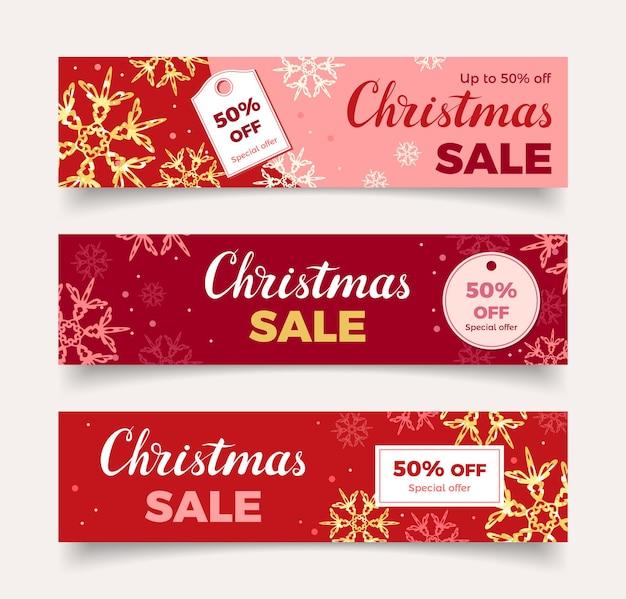 Bannières rouges de vente de noël sertie de flocons de neige dorés et de lettrage