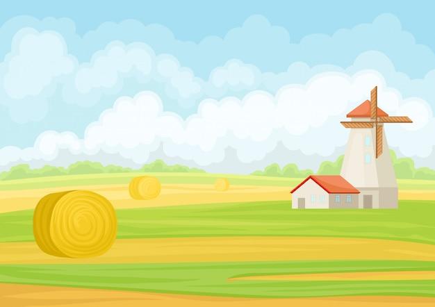 Beau paysage avec moulin et botte de foin.