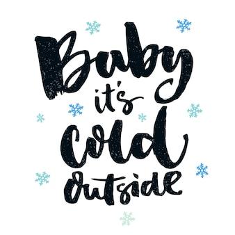 Bébé, il fait froid dehors. citation d'hiver romantique pour cartes de vœux et art mural. brossez la typographie, les mots noirs sur fond blanc avec des flocons de neige bleus.